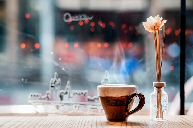 Чашка горячего эспрессо на деревянном столе в кофейне с космосом экземпляра.