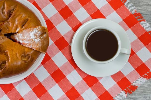 テーブルの上の熱い新鮮なお茶とおいしい自家製ケーキのカップ。上面写真