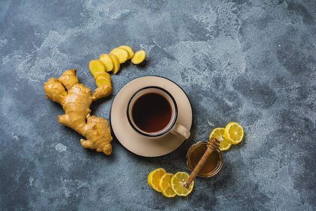 濃い灰色の背景にレモンと蜂蜜とホットジンジャーティーのカップ。上面図。