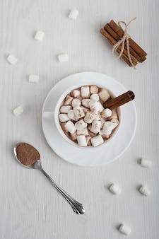 Чашка горячего домашнего напитка какао подается на тарелке с зефиром и корицей на белом дереве. вид сверху