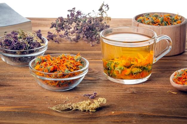白い背景の上の木製のテーブルにキンセンカの花の熱い注入のカップ。癒しのハーブのコレクション。