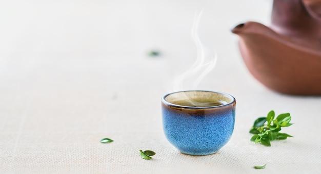 熱い日本の緑茶のカップ。カップにセレクティブフォーカス。一杯のお茶から蒸気が発生します。テーブルの上のティーポットと緑の葉。コピースペースのクローズアップ。お茶会のアイデア、ミニマリズム