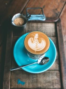 ヴィンテージの木製のテーブルで熱いラテアートコーヒーのカップ。