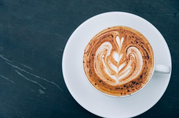 木製のテーブルの上の熱いラテアートコーヒーのカップ