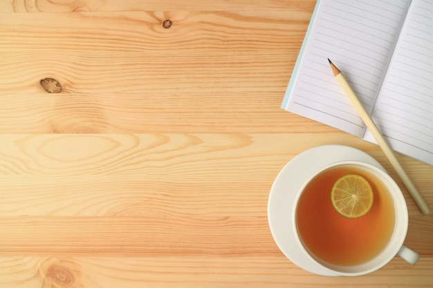 Чашка горячего лаймового чая с записной книжкой и карандашом на деревянном столе