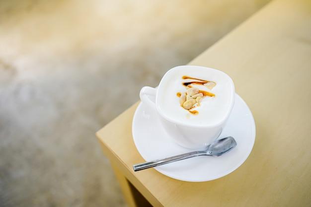 Чашка горячего молока с красивой молочной пеной и покрытая ломтиком миндаля и медовым сиропом на деревянном столе