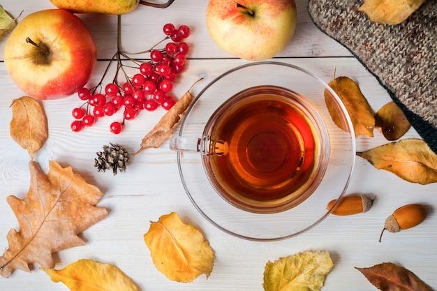 木製の白い表面に熱いお茶と紅葉と果物のカップ。暖かいジャケット、コーン、どんぐり、ベリー。