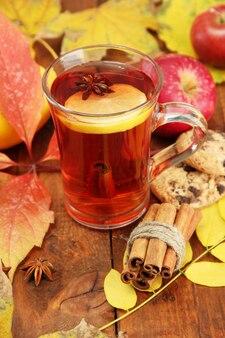 Чашка горячего чая и осенние листья, на коричневом фоне
