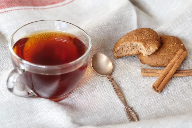 一杯の熱いお茶とシナモンとオートミールのクッキー
