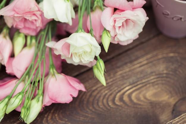 Чашка горячего чая и розовые цветы эустомы