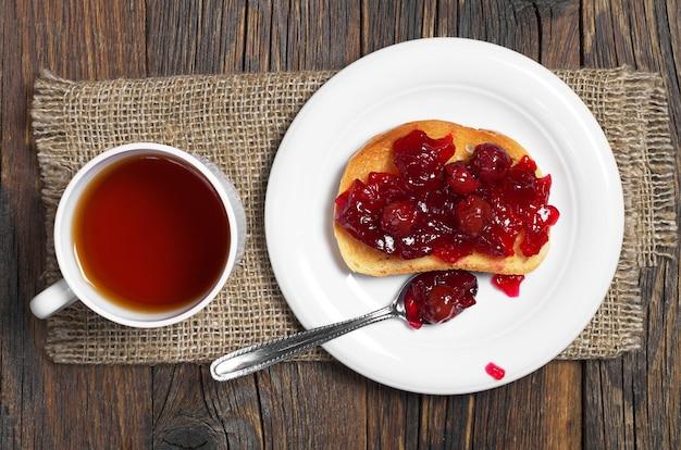 朝食、上面図のチェリージャムと熱いお茶とロースト白パンのカップ