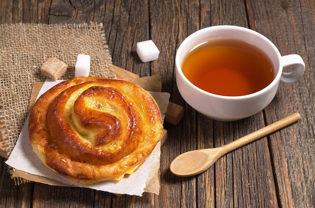 소박한 나무 테이블에 잼을 넣은 뜨거운 차와 달콤한 롤빵