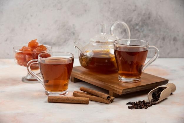Чашка горячего чая, чайник и сладкое варенье из айвы на деревянной доске.