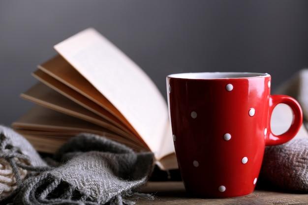 책과 격자 무늬 테이블에 뜨거운 차 한잔