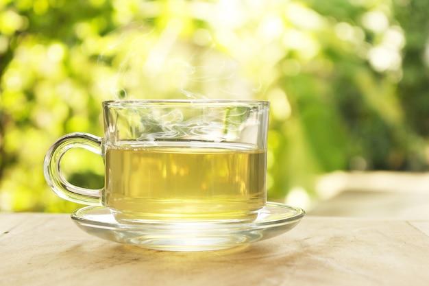 Чашка горячего чая с дымом на размытом фоне природы.