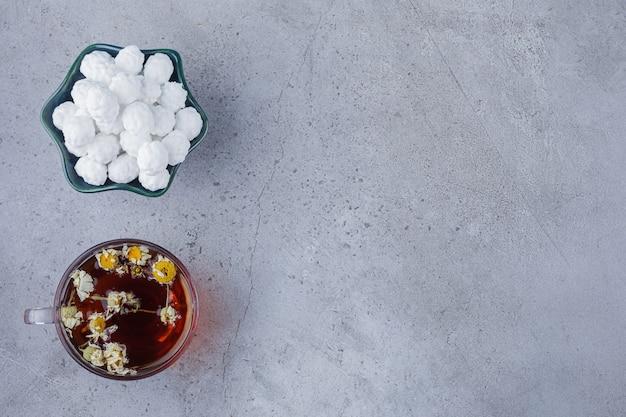 Чашка горячего чая с белой миской белых конфет на каменном фоне.