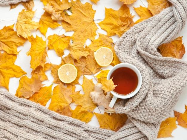 黄色いカエデの紅葉と生姜のレモンと熱いお茶のカップ。秋の季節のフラットレイホットドリンク組成物。秋の背景として灰色のスカーフ。