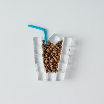 Чашка ледяного кофе из кубиков льда и кофейных зерен