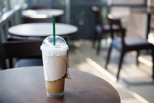 Чашка кофе со льдом на деревянном столе в кафе