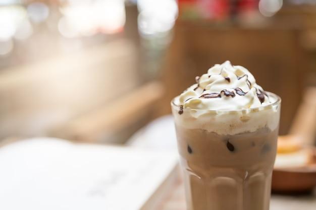 木製のテーブルの背景に氷のモカコーヒーのカップ。飲食物のコンセプト