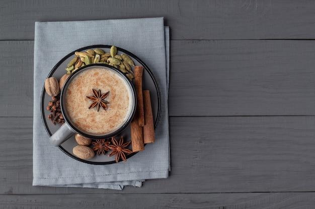 Чашка индийского чая масала и специй на сером деревянном столе, вид сверху с копией пространства