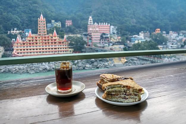 ガンジス川とインドの寺院の美しい背景にインド茶とベジタリアンサンドイッチのカップ。観光朝食。美しい景色を望むカフェ。野菜のレイヤードサンドイッチ。ティーバッグ