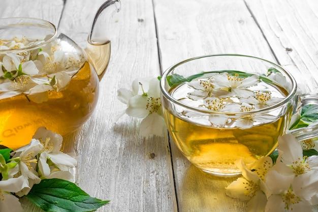 Чашка жасминового чая с чайником и цветами жасмина на деревенском деревянном фоне