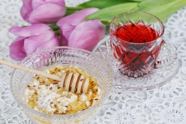 Чашка красного чая каркадех, творог плюс овсяные хлопья, льняное семя и мед на столе с фиолетовыми тюльпанами