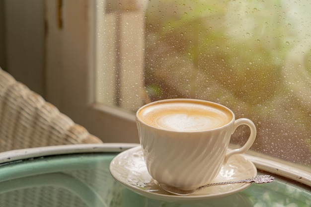 아침에 비가 온 후 빗방울이 떨어지는 창문 가까이에 라떼 아트가 있는 라떼 커피 한 잔