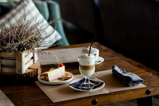 라떼 마끼아또 한잔. 라떼 커피 한 잔과 딸기 치즈 케이크 한 조각. 개념적 맛있는 달콤한 아침 식사. 우유 거품과 코코아, 계피 가루와 함께 유리에 커피 라떼.톤 이미지입니다.