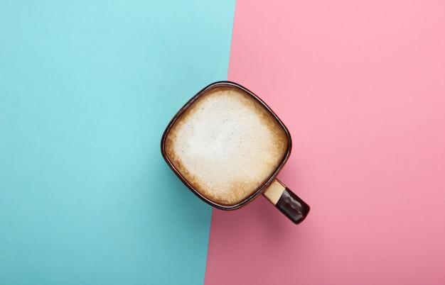 ピンクブルーのパステルカラーの背景にラテまたはカプチーノのカップ。ミルクコーヒー。上面図 Premium写真