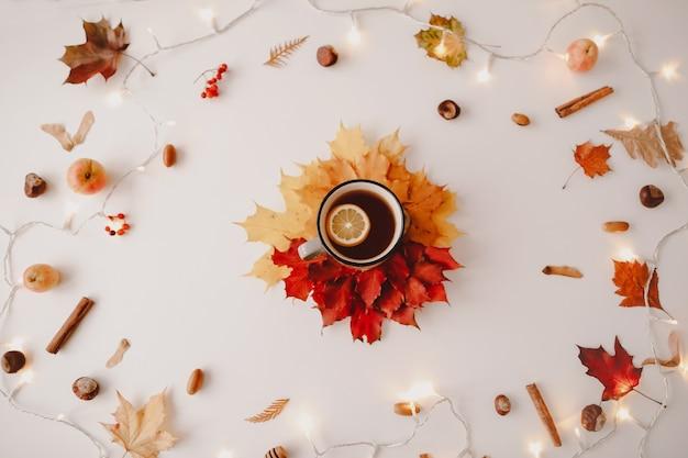 Чашка чая с лимоном в рамке из оранжевых и красных листьев творческий осенний узор, открытка, копия пространства, вид сверху