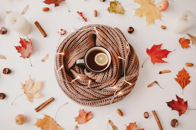 Чашка чая с лимоном в рамке из оранжевых и красных листьев креативный осенний узор