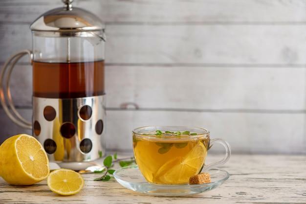 サトウキビ砂糖、フレンチプレス、ライト木製テーブルのレモンスライスとレモン茶のカップ