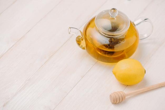 白い木製の背景に蜂蜜とレモンティーのカップ。