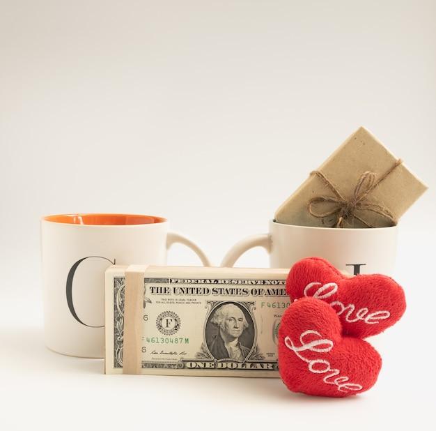 愛のカップ、赤いハートのアイコンが付いた2つのコーヒーカップ、ドル紙幣、白い背景の上のギフトボックス、バレンタインのコンセプト