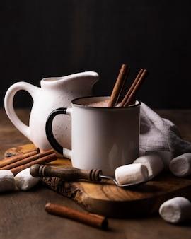 木の板にシナモンとマシュマロ飲み物のカップ