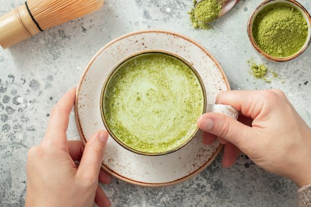 Чашка зеленого чая матча в руках женщины.