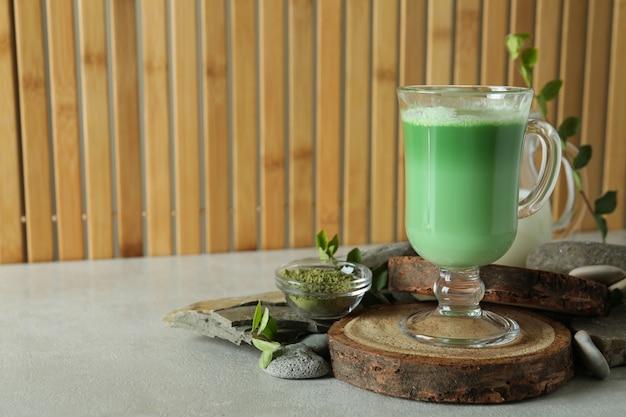 Чашка матча латте и аксессуары для приготовления на бамбуковом фоне
