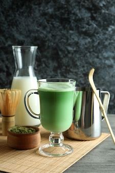 Чашка матча латте и аксессуары для приготовления на сером текстурированном столе