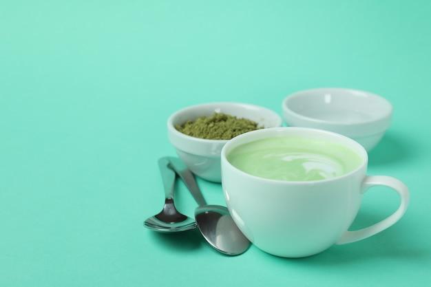 Чашка матча латте и аксессуары для приготовления на мятном фоне