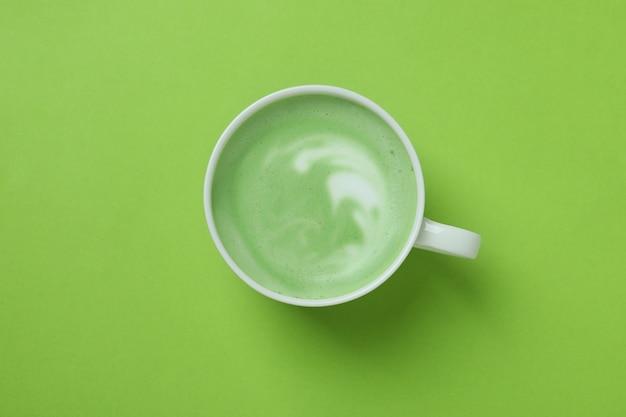Чашка матча латте на зеленом фоне