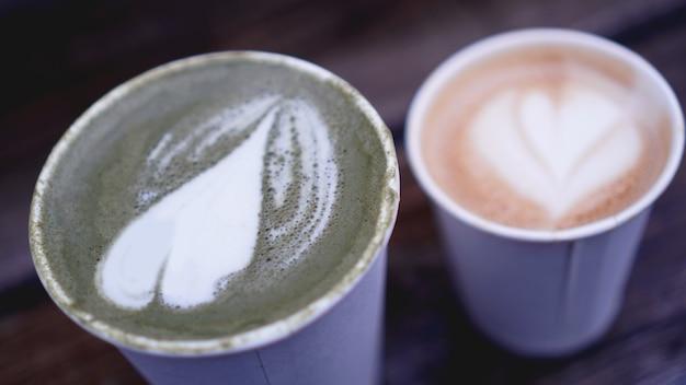 Чашка чая матча с латте-артом и капучино в бумажном стаканчике на деревянном фоне. размытый фон.