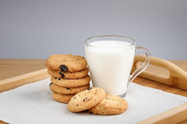 Чашка молока и печенье с изюмом на деревянном подносе