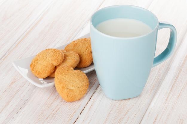 흰색 나무 테이블에 우유와 하트 모양의 쿠키 한 컵