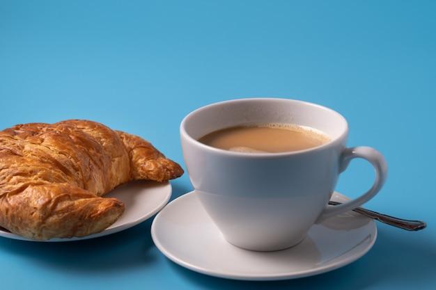 Чашка кофе с молоком и круассан на синем фоне, скопируйте пространство для текста.