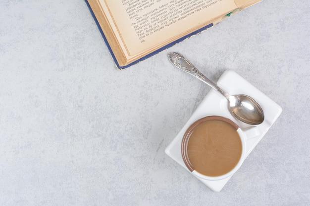 石の表面にミルクコーヒー、スプーン、本を一杯。高品質の写真