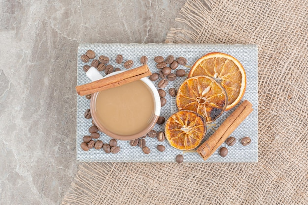 Чашка кофе с молоком с кофейными зернами и дольками апельсина на книге. фото высокого качества