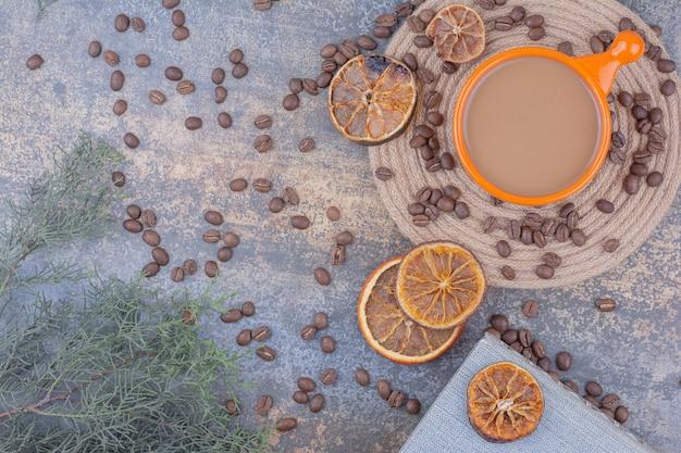Чашка кофе с молоком с кофейными зернами и апельсинами. фото высокого качества