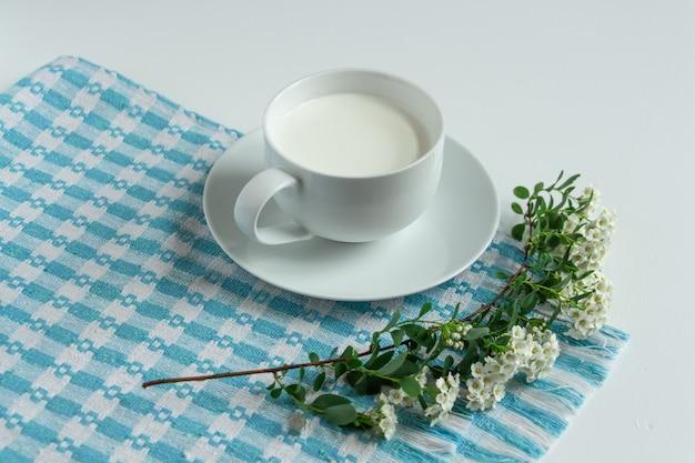 파란색 체크 무늬 냅킨에 흰색 바탕에 우유 한잔